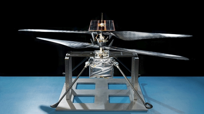 This image of the flight model of NASA's Mars Helicopter was taken on Feb. 14, 2019, in a cleanroom at JPL. The aluminum base plate, side posts and crossbeam around the helicopter protect its landing legs and the attachment points that will hold it to the belly of the Mars 2020 rover. (Credits: NASA/JPL-Caltech)