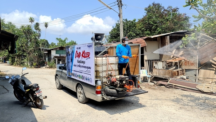 A volunteer sprays disinfectant as the truck drives slowly through the village.