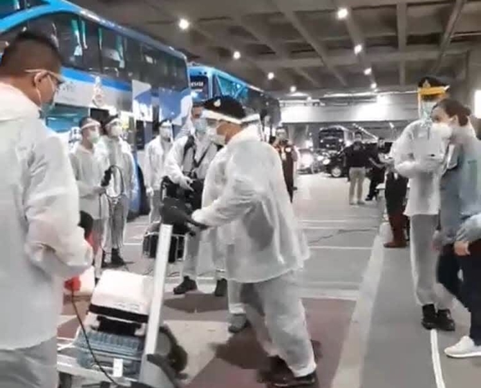 The passengers and their baggage are thoroughly checked and spayed with disinfectant before boarding the bus to quarantine facilities.