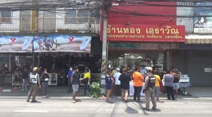 A gold shop owner in Chiang Mai hands out rice packs and necessities to the people.
