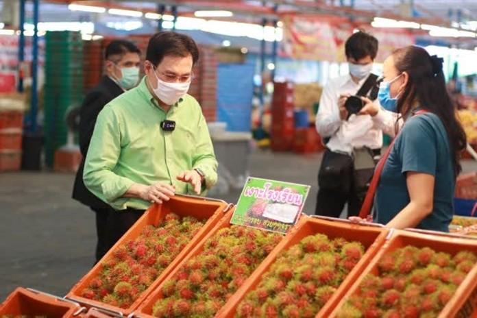 Minister of Commerce, Jurin Laksanawisit talks to a Rambutan seller at the Talaad Thai wholesale fresh market.