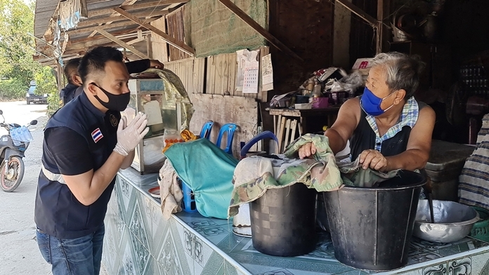 Dr. Satira Puakpraphan greets a villager and politely asks for permission to spray disinfectant in and around her home.