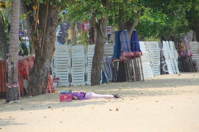 A Thai woman taking a nap on the beach after a long and tiring walk.