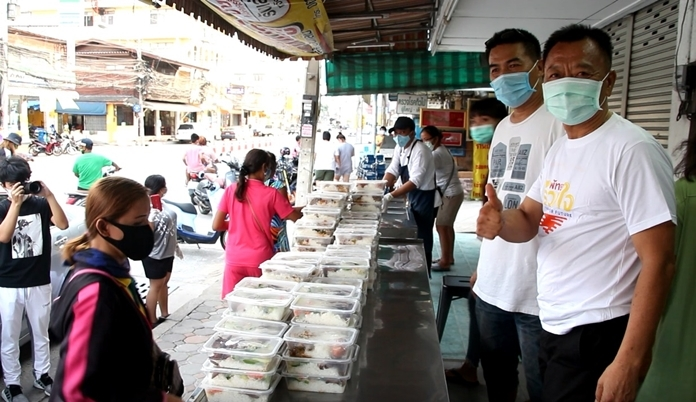 Former Pattaya mayor Niran Watttanasartsathorn together with staff distribute food to those in need in front of the Thai Sanguan rice & curry shop.