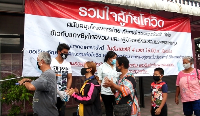 """The public had to wash their hands with sanitizer gel before approaching the distribution stands. The sign says, """"United in our fight against the dangers of COVID-19""""."""