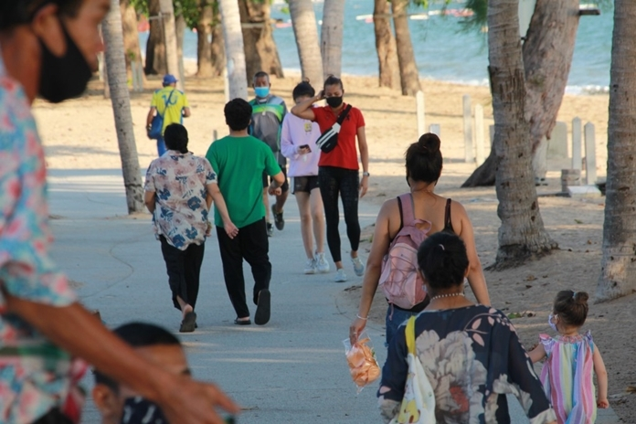 Tourists are walking along the clean and well paved footpath for exercises and leisure on a sunny day on Jomtien Beach,Pattaya City.