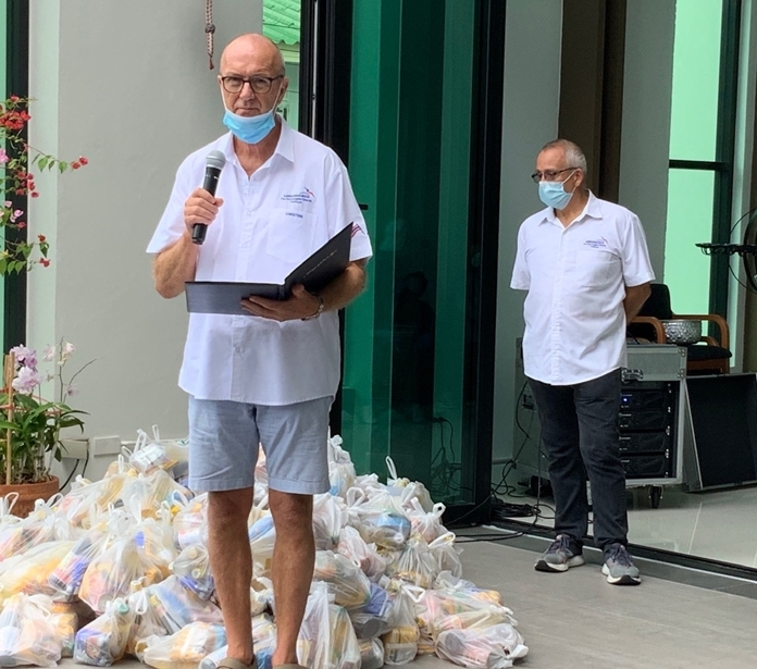 Rev. Annstein Lothe blesses the congregation as Hans Konrad Nyvolllooks at the huge pile of foodstuffs ready for distribution.