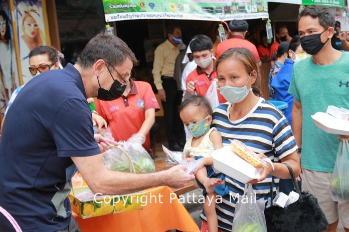 Enrico Egli hands out 100 baht to help people with their daily necessities.