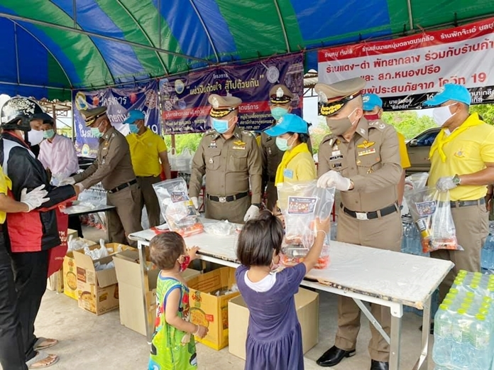 Pol. Gen. Montri Yimyaem, commander of Chonburi Region 2, and officers distribute care packages to the people of Nongprue community.
