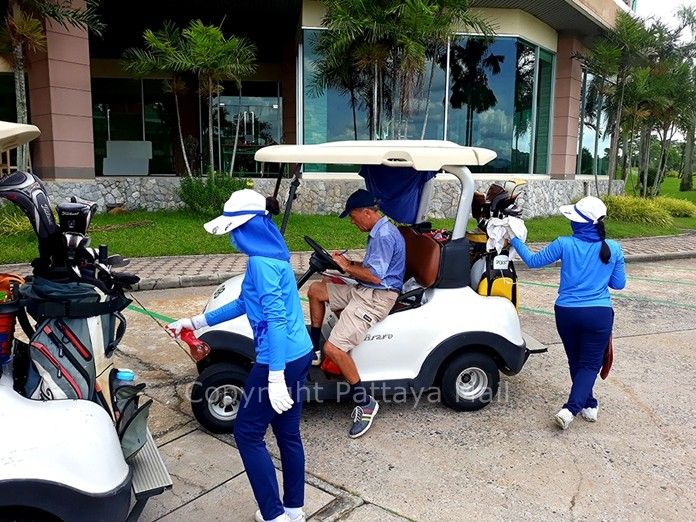 Caddies spray disinfectant on carts at half way.