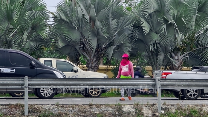 Pink shirted donut sellers dodge moving traffic when the lights turn green.