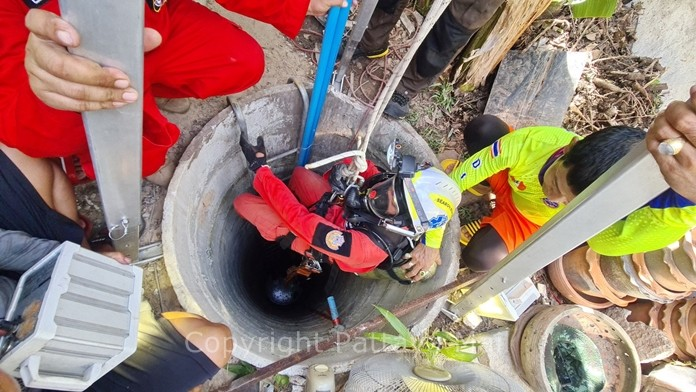A Sattahip rescue worker is lowered into the well to retrieve the bodies of Nared Pilan and his cousin Komkid Pranut who died of apparent hydrogen sulfide poisoning while dredging a well behind their house.