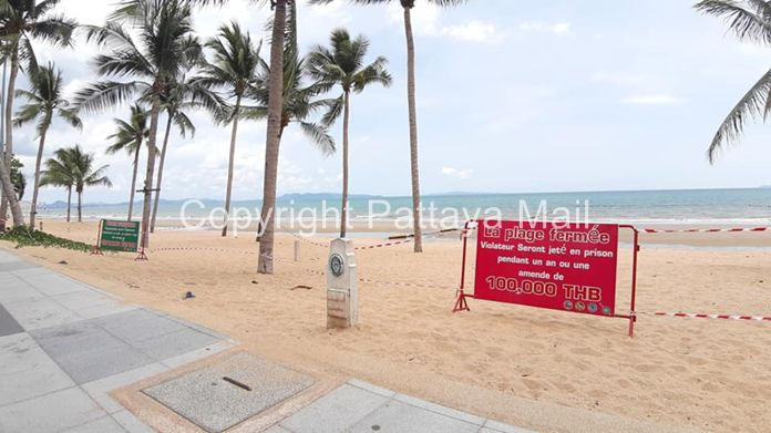 Jomtien Beach with tape and signboards in French and many more languages explaining the beach use prohibition and punishment for violators.