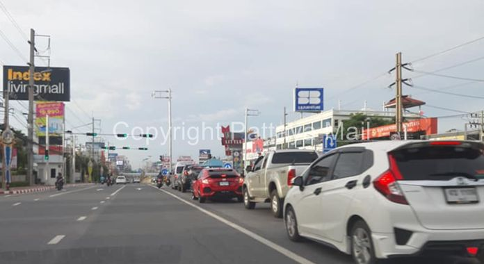 A long queue of vehicles waiting at a red light at the Soi Siam Country Club entrance showing that people from the other side are now driving in and out of Pattaya City for works in the morning and get back to their homes in the evening.