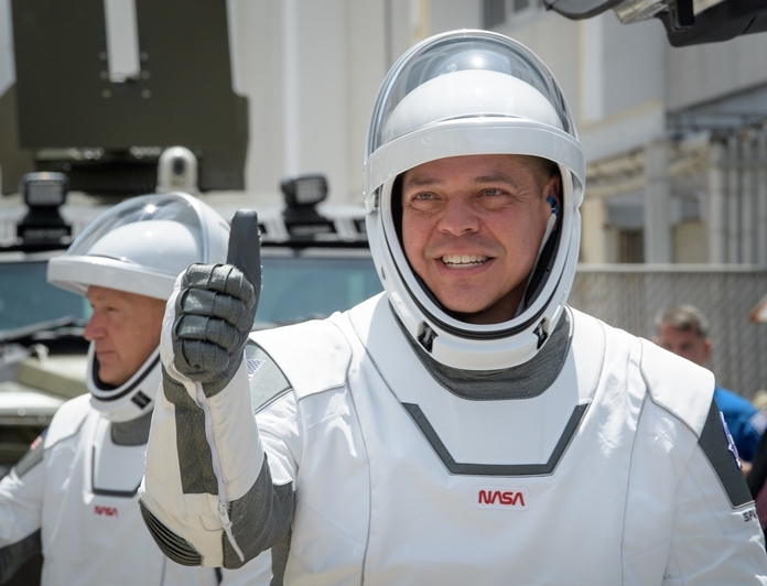 NASA astronauts Robert Behnken, foreground, and Douglas Hurley, wearing SpaceX spacesuits, are seen as they depart the Neil A. Armstrong Operations and Checkout Building.