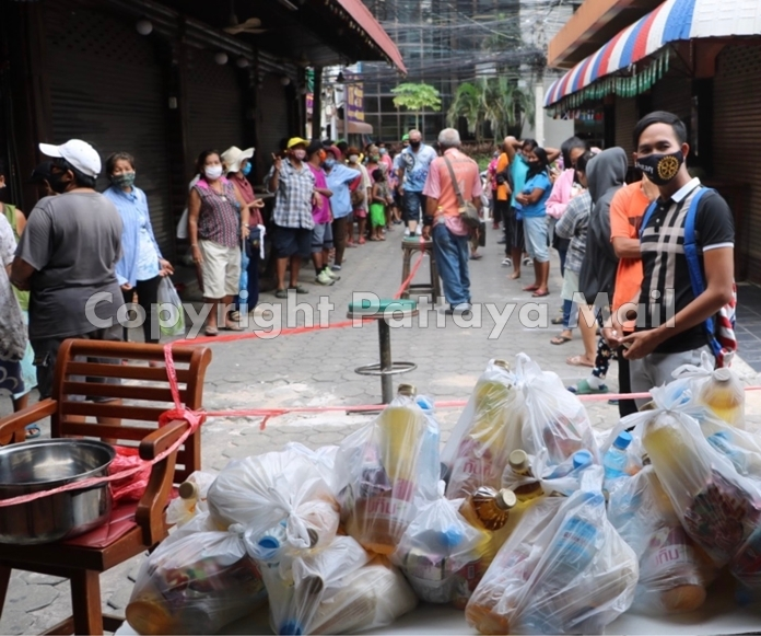 Hundreds of people line the soi waiting for the distribution to begin.