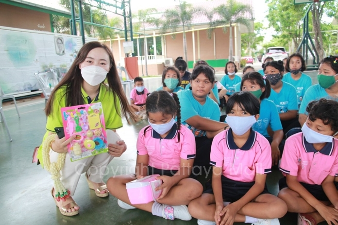 Beautiful women from the Chinese Tourists Assist Centre hand out toys to the children.