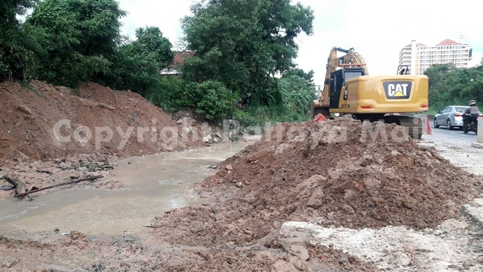 Contractors laying new drainage pipes in East Pattaya brought in heavy equipment to build a temporary berm to block storm runoff from flooding homes around Soi Khao Talo.