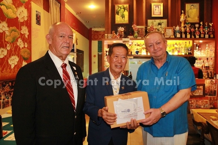 District Governor Maruai Jintabunditwong presents a box of face masks to President-Elect Peter Marsh of the Rotary Club of Jomtien-Pattaya, as Assistant Governor Rodney Charman looks on.