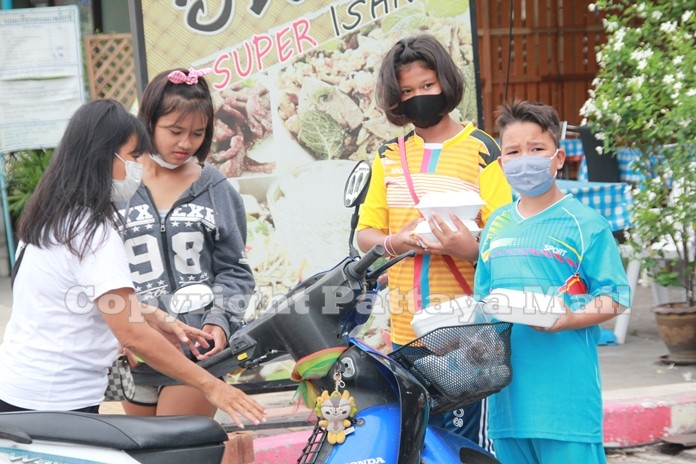 This family prepares to ride their motorbike home after receiving their share of food and water.