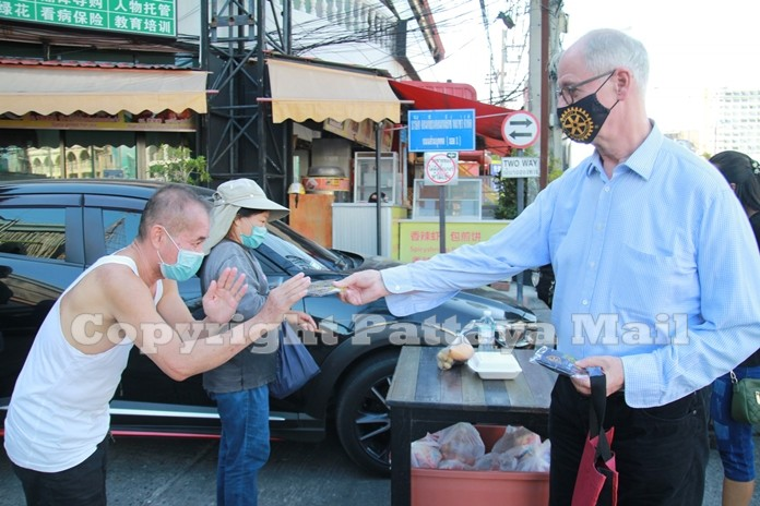 Pres. Dieter Reigber gives a Rotary face mask to one of the residents of the area.