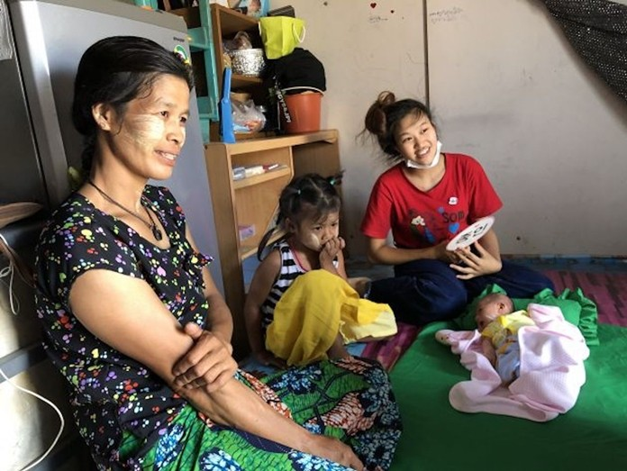 Emoon with her family inside their home in Chiang Mai.
