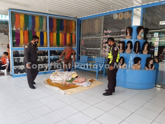 Municipal officers collect two homeless men camped out in front of a South Pattaya salon.