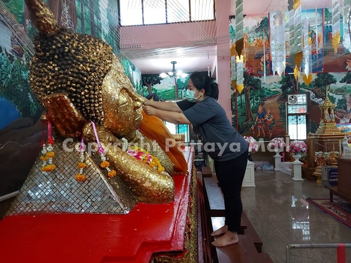 Believers gild the Luang Phor To statue at Wat Suttawas