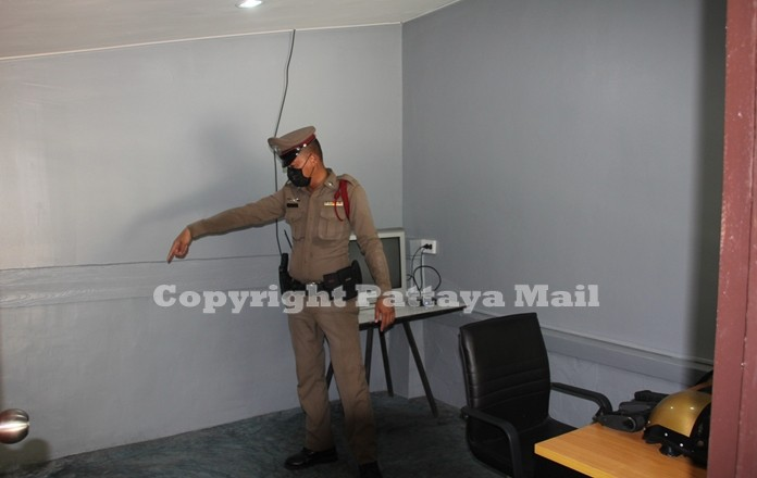 A policeman points to an area that needs repair at the public service point.