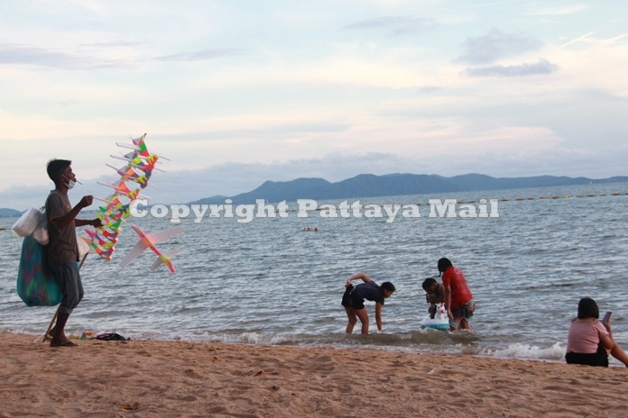 A toy airplane peddler sells his wares along the beach as happy holiday makers play in the sea.