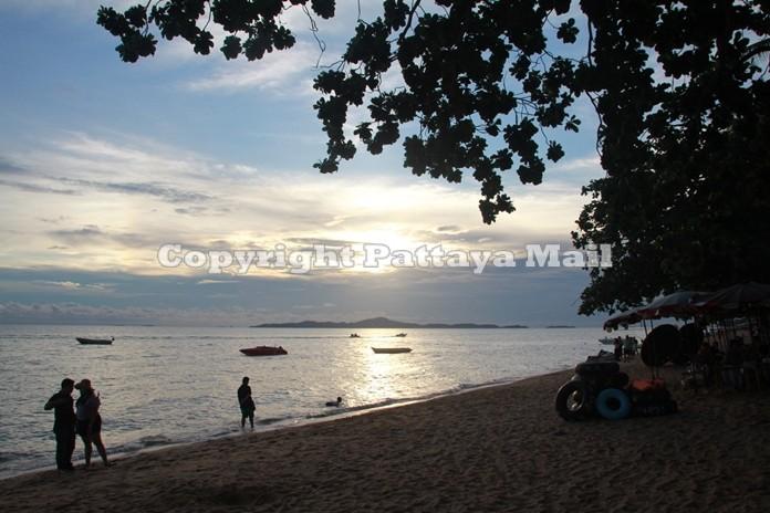 As the sun sets over Pattaya Bay, lovers stroll along the beach cherishing that romantic moment.