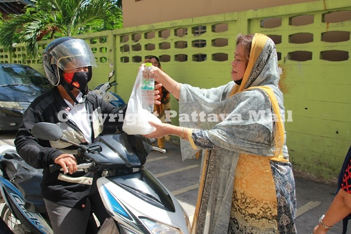 Wanna Malhotra gives a package of food to a passing motorbike rider.