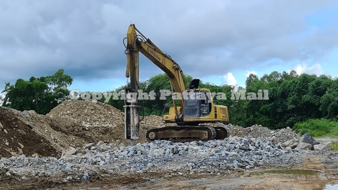 The rock crusher at work unconcerned for the heavy damage it was causing to the neighboring temple.
