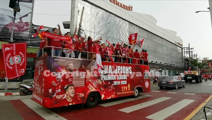 Liverpool FC fans sing and wave flags as they ride the replica of the English victory bus around Pattaya.