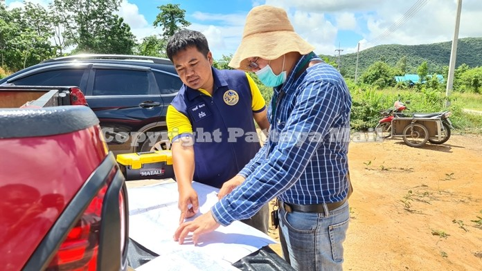 Worarit Jungbavorn, Bang Saray district headman and Somchok Siri, Surveyor from the Sattahip Land Department inspect a map to determine whether there was any encroachment on public land.