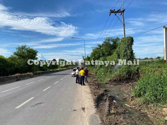 An otherwise picturesque railway road is marred by clogged waterways and garbage dumped on the side of the road.