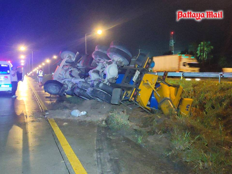 A cement truck lies on its side after skidding off Pattaya-Rayong Highway 36. The driver was unhurt.